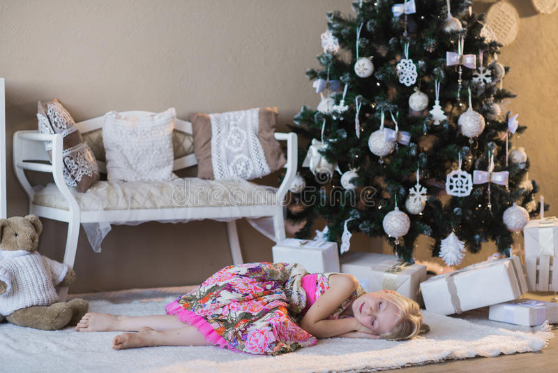 Het meisje dichtbij de Kerstboom was slaap die op Kerstman, de voorbereiding voor de vakantie, verpakking, dozen, Christm wachten royalty-vrije stock foto's