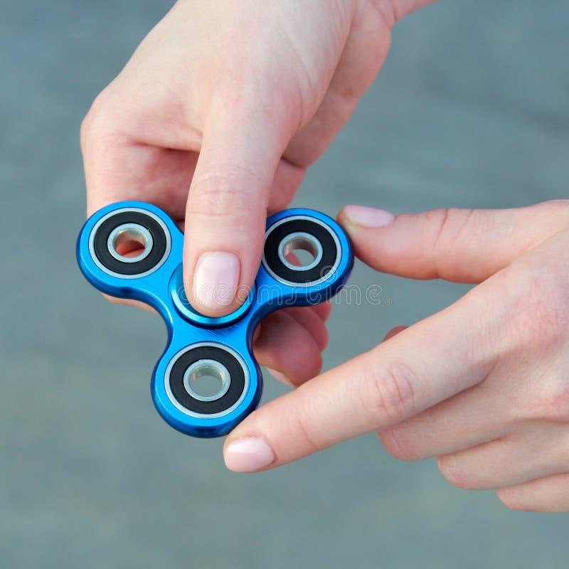 Het meisje die blauwe metaalspinner in handen op de straat spelen, vrouwelijke handen die populair friemelt spinnerstuk speelgoed stock afbeeldingen