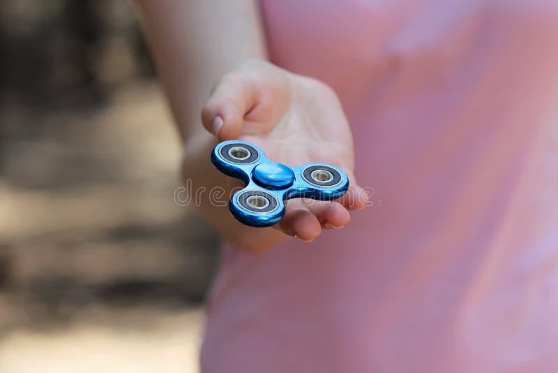 het meisje die blauwe metaalspinner in handen op de straat spelen, vrouwelijke handen die populair friemelt spinnerstuk speelgoed stock foto