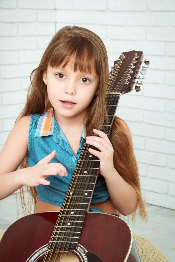 Het meisje die de gitaar spelen en zingt stock afbeelding