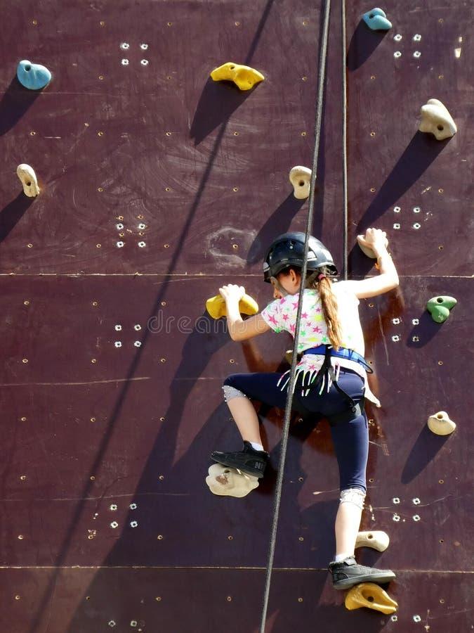 Het meisje die een verticale rotsmuur met helm op haar hoofd beklimmen bond veilig met kabel voor bescherming stock afbeeldingen