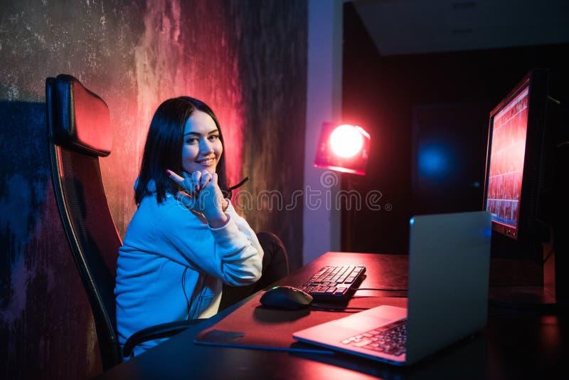 Het meisje die gamer met haar vingers aan monitors, concept schieten virtuele werkelijkheid, gokken en esports stock afbeeldingen