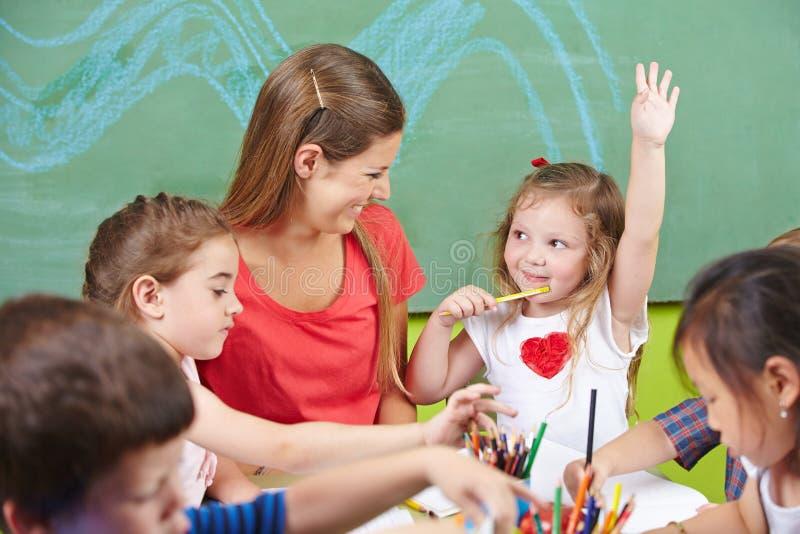 Het meisje die haar opheffen dient kleuterschool in stock fotografie