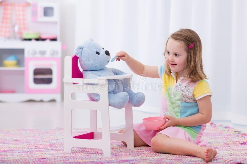 Het meisje die haar stuk speelgoed voeden draagt stock fotografie