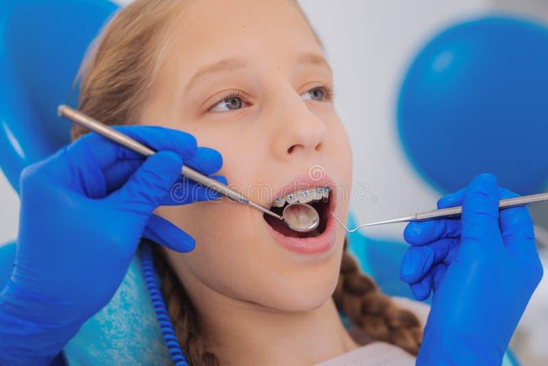 Het meisje die haar tanden hebben onderzocht terwijl het zitten in een tandkliniek stock foto