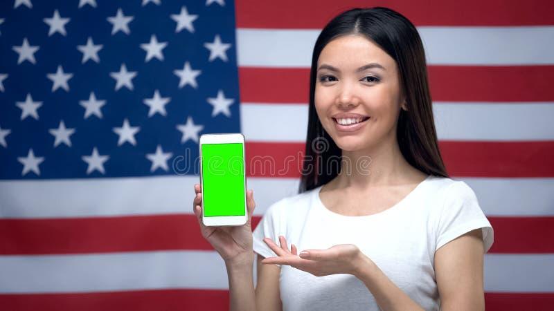 Het meisje die smartphone met het groene scherm, de V.S. tonen markeert op achtergrond, vertaler app stock afbeeldingen