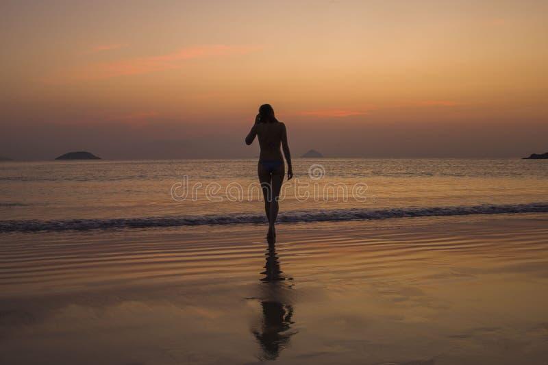 Het meisje die uit het overzees op de achtergrond van zonsopgang en zonsondergangzonstralen komen stelt in de schaduw stock foto