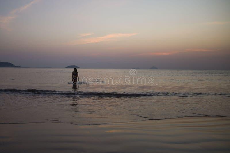 Het meisje die uit het overzees op de achtergrond van zonsopgang en zonsondergangzonstralen komen stelt in de schaduw royalty-vrije stock afbeelding