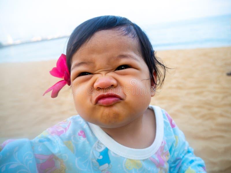 Het meisje die van Azië grappig gezicht en rode bloemen in haar oor maken Haar zitting op het strand en het kijken gelukkig stock afbeeldingen