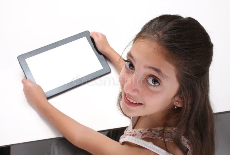 Het meisje die van de Beaitiful pre-tiener een tabletcomputer met behulp van stock fotografie