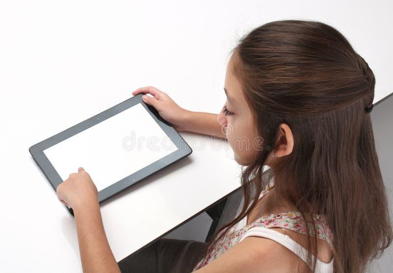 Het meisje die van de Beaitiful pre-tiener een tabletcomputer met behulp van stock foto's