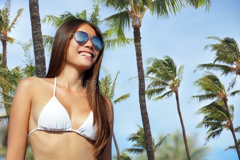 Het meisje die van de bikini zonnebril op palmstrand dragen royalty-vrije stock fotografie