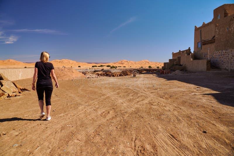 Het meisje die van de blondetoerist een gang hebben dichtbij grote zandduinen van de woestijn van de Sahara stock afbeelding