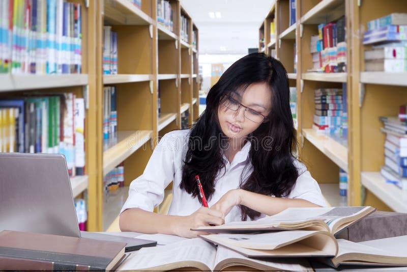 Het meisje die van de middelbare schoolstudent in bibliotheek bestuderen stock afbeeldingen