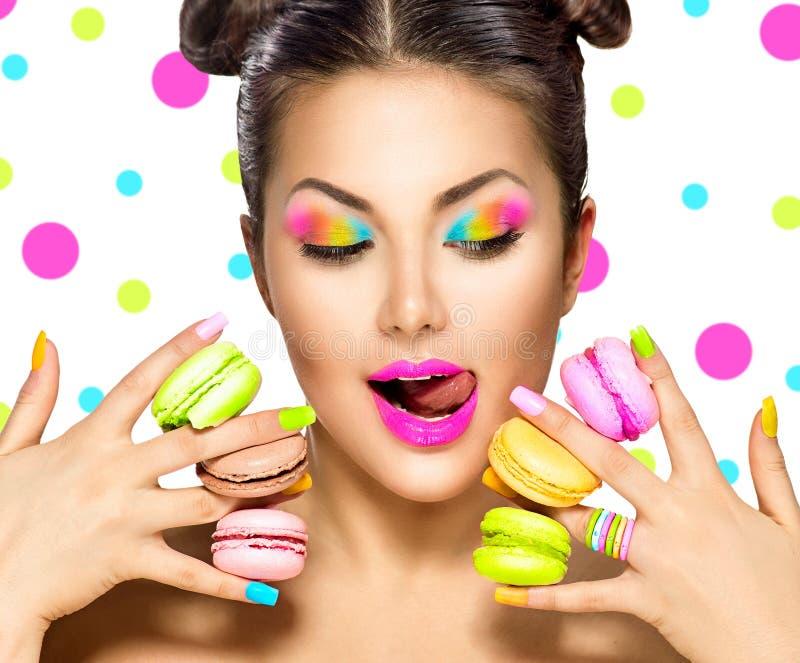 Het meisje die van de schoonheidsmannequin kleurrijke makarons nemen stock foto's