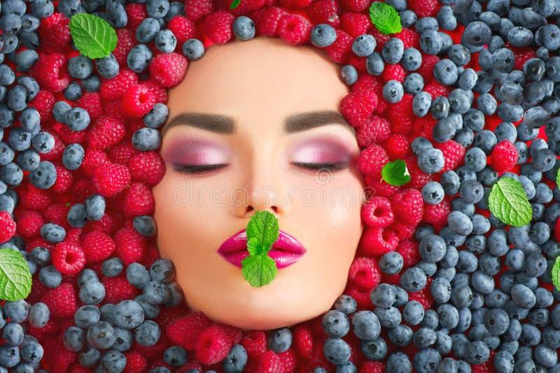 Het meisje die van de schoonheidsmannequin in verse rijpe bessen liggen Gezicht in kleurrijke bessenclose-up Mooie make-up, sappi stock fotografie
