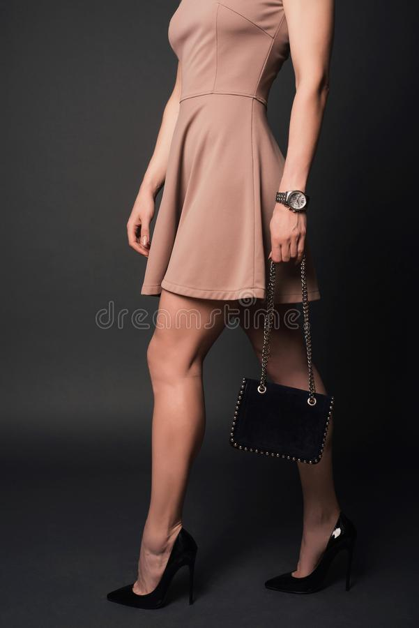 Het meisje die van de stijlmanier kledings zwarte schoenen dragen die kleine handtas met details houden stock afbeeldingen