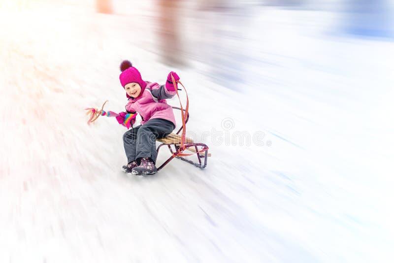 Het meisje die van Hapycutee litlle pret het sledging van heuvel op heldere zonnige dag hebben Kind die snel op sleeën zich berga royalty-vrije stock afbeeldingen