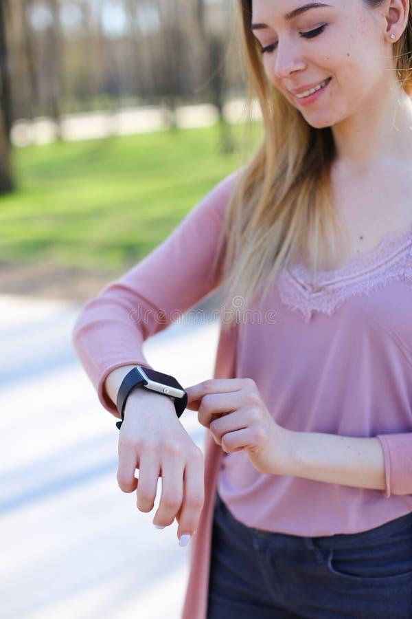 Het meisje die van Nice in park lopen en slim horloge met behulp van stock afbeelding