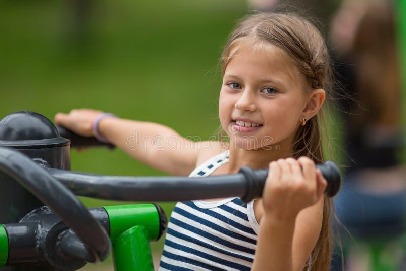 Het meisje die van tien jaar oefeningen in openlucht doen bij een sportengrond royalty-vrije stock foto