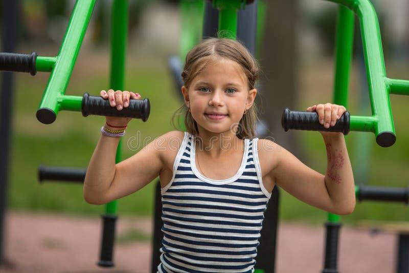Het meisje die van tien jaar oefeningen in openlucht doen bij een sportengrond Sport royalty-vrije stock foto
