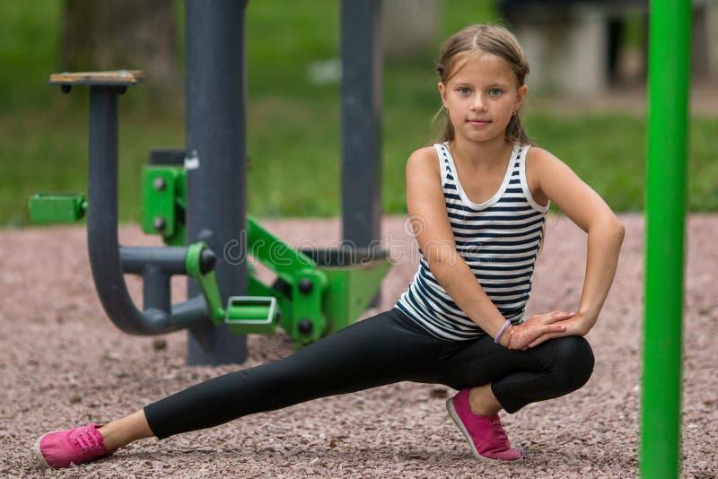 Het meisje die van tien jaar oefeningen in openlucht doen bij een sportengrond Sport royalty-vrije stock afbeelding