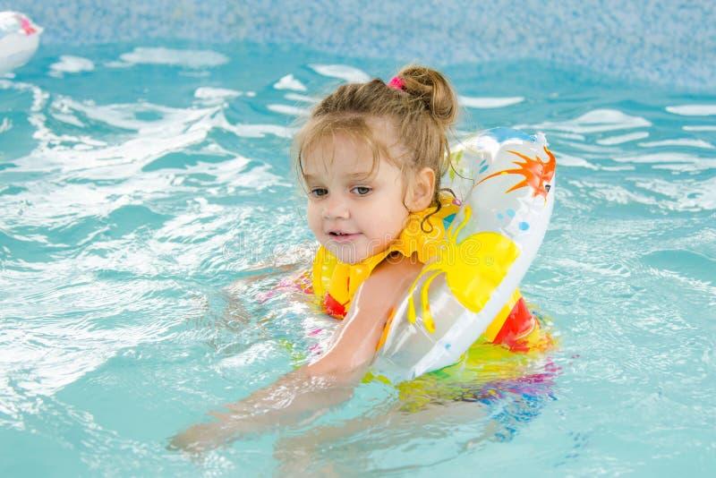 Het meisje die van vier jaar in de pool drijven stock afbeeldingen