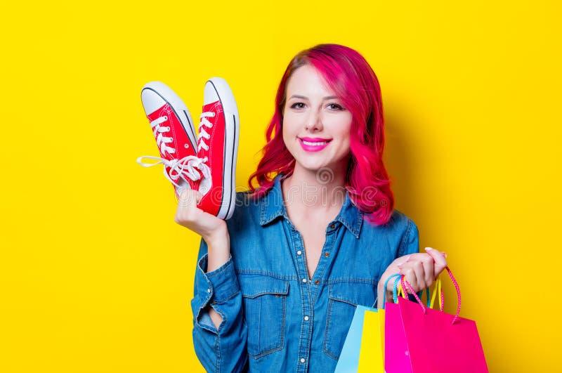 Het meisje die het winkelen houden doet en rode gumshoes in zakken royalty-vrije stock foto's