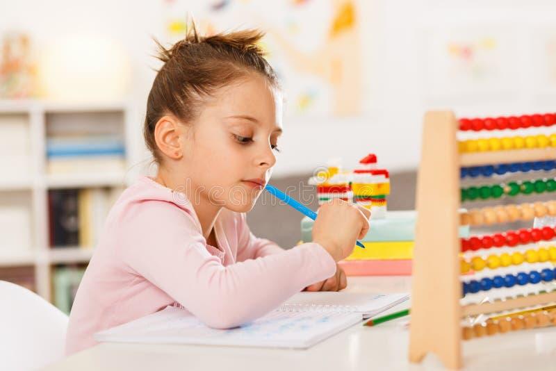 Het meisje doet thuiswerk stock foto