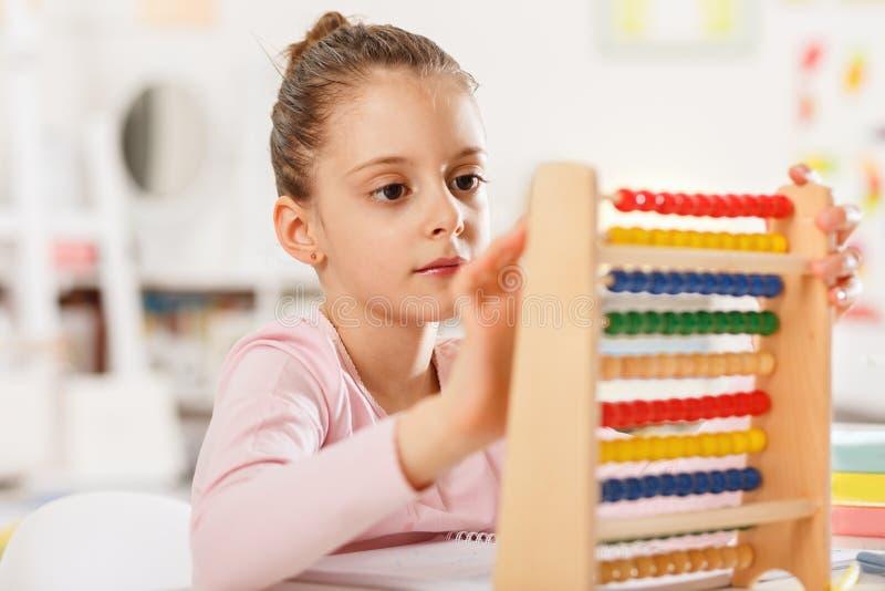Het meisje doet thuiswerk stock fotografie