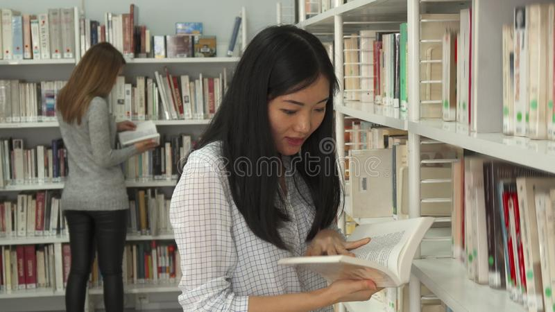 Het meisje draait pagina's bij de bibliotheek royalty-vrije stock afbeelding