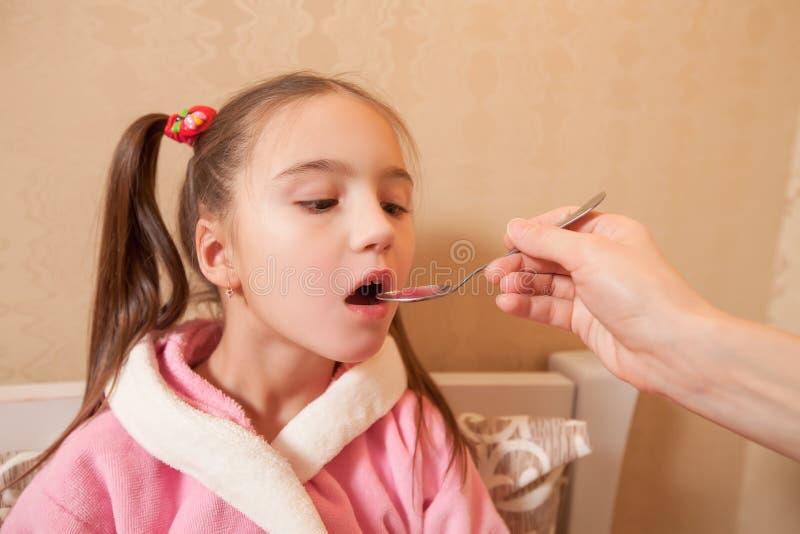 Het meisje drinkt mengsel van een lepel royalty-vrije stock foto's