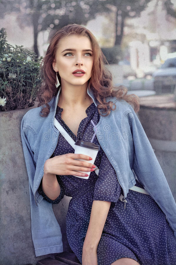 Het meisje drinkt in openlucht koffie royalty-vrije stock afbeelding