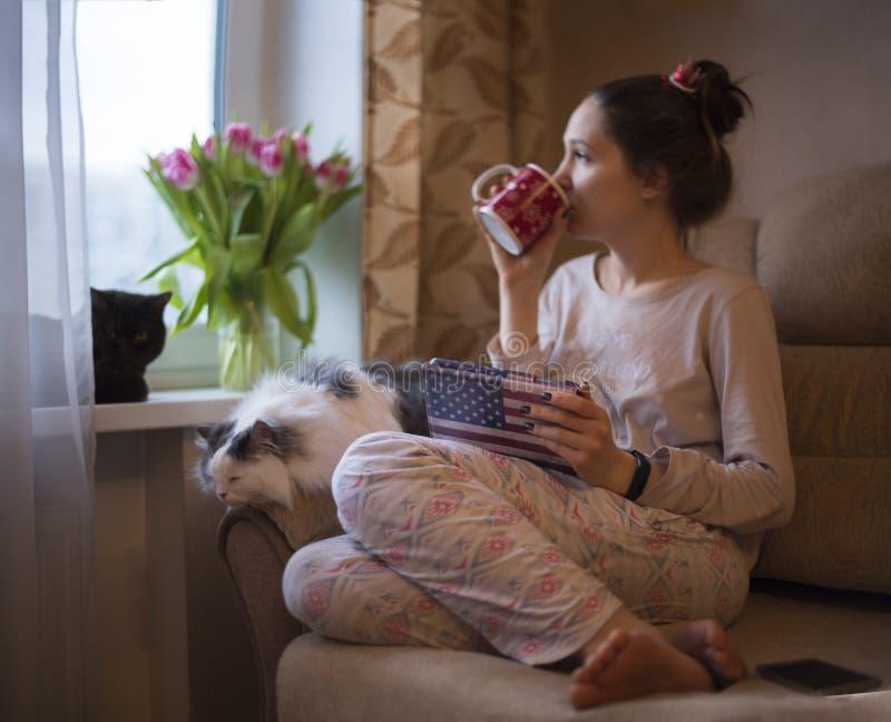 Het meisje drinkt thee en dromen van de lente royalty-vrije stock foto