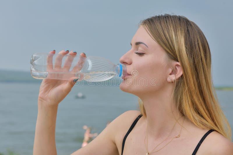 Het meisje drinkt water stock afbeelding