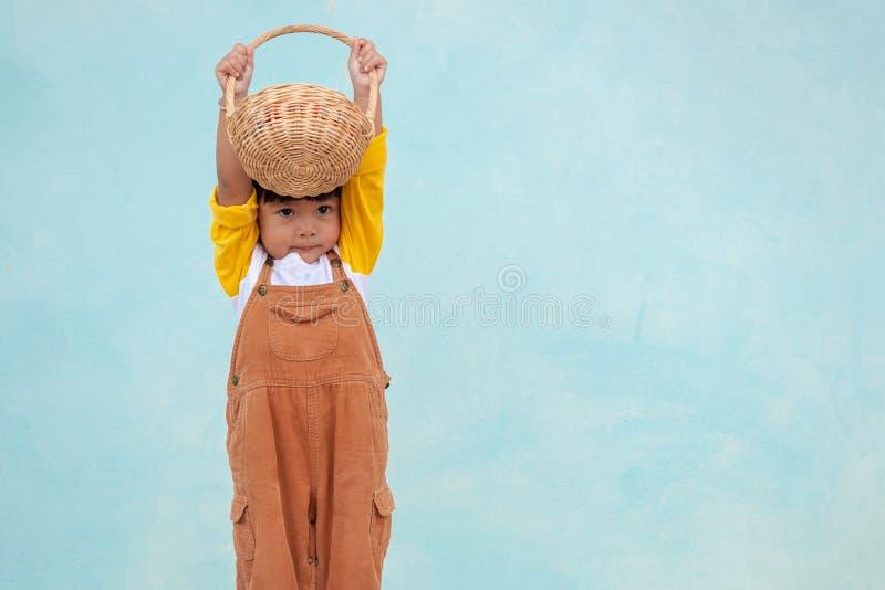 Het meisje droeg een bruine gekleurde slabkleding, hief twee handen op en hief de houten mand over het hoofd op royalty-vrije stock foto