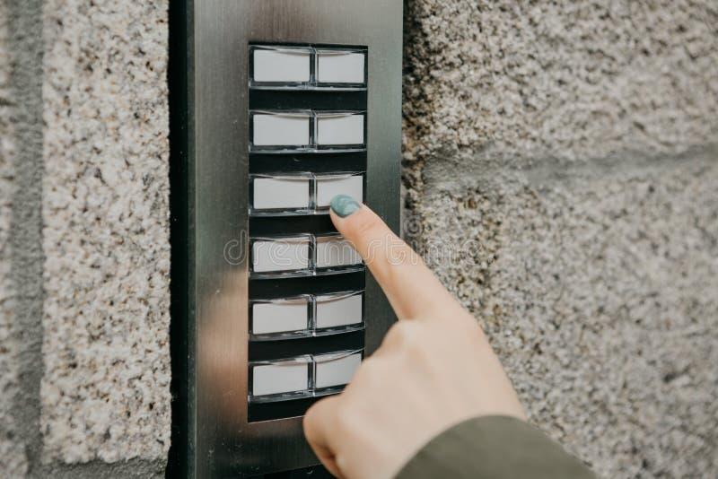 Het meisje duwt de doorphoneknoop of roept de intercom stock foto's