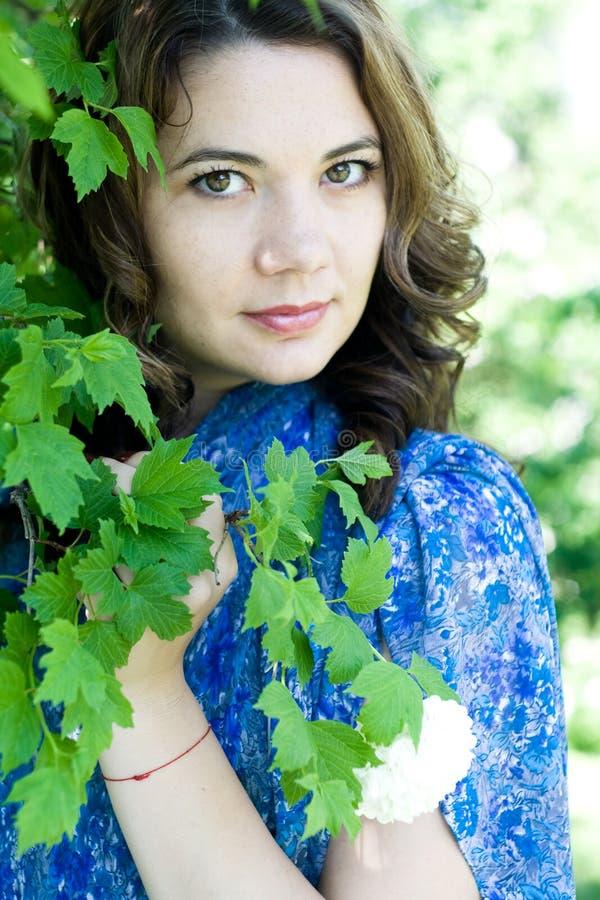Het meisje in een blauwe kleding die een tak met bloemen houden royalty-vrije stock afbeelding