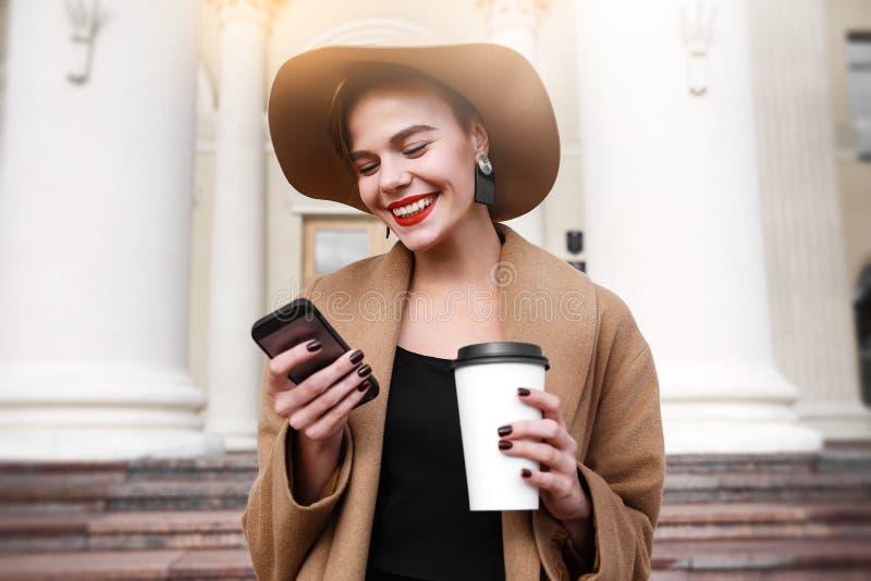Het meisje in een bruine laag een bruine hoed loopt en stelt in het stadsbinnenland Het meisje is het glimlachen, controlerend ha stock fotografie