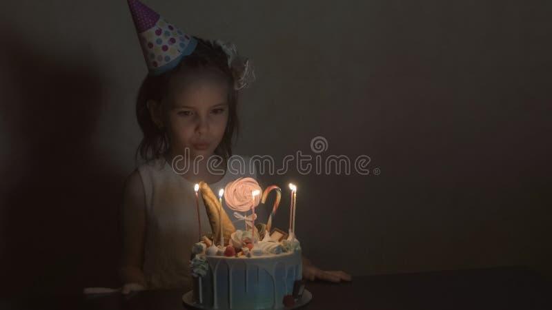 Het meisje in een feestelijke hoedenslag schouwt uit op een verjaardagscake het concept van de kinderen` s verjaardag stock foto's