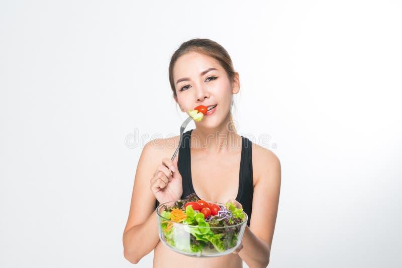 Het meisje in een geschiktheidsreeks houdt een saladekom stock afbeeldingen