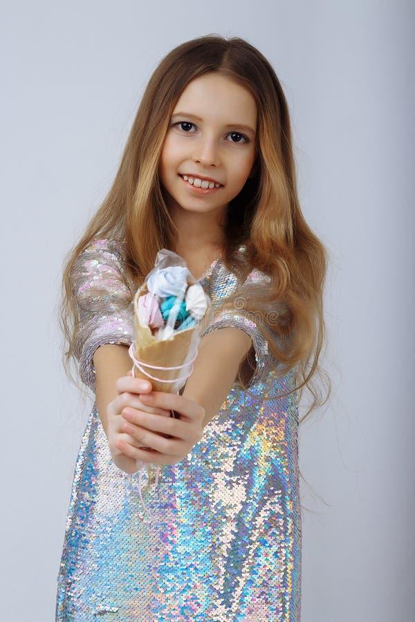 Het meisje, in een glanzende en iriserende die kleding die, van lovertjes wordt gemaakt, een suikergoed, een heemst, op een stok  royalty-vrije stock foto's