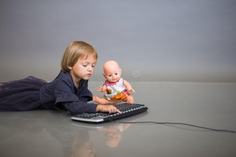 Het meisje in een grijze kleding ligt met een pop op een grijze achtergrond en speelt met het toetsenbord van de computer royalty-vrije stock foto