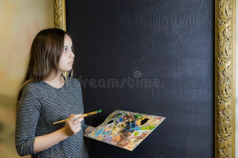 Het meisje in een grijze kleding met een leeswijzer en een palet voor het beeld royalty-vrije stock fotografie