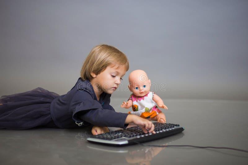 Het meisje in een grijze kleding op spelen grijze als achtergrond met het toetsenbord van de computer en een pop royalty-vrije stock afbeelding