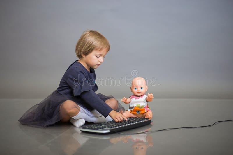Het meisje in een grijze kleding zit met een pop op een grijze achtergrond en speelt met het toetsenbord van de computer royalty-vrije stock foto