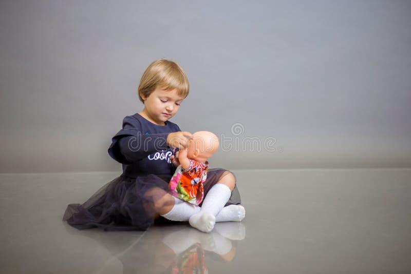 Het meisje in een grijze kleding zit op een grijze achtergrond en speelt met een poppenbaby - pop stock afbeeldingen