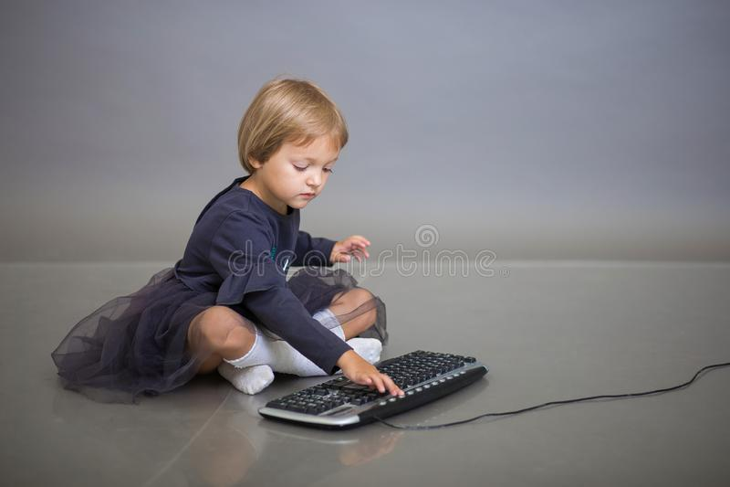 Het meisje in een grijze kleding zit op een grijze achtergrond en speelt met het toetsenbord van de computer stock fotografie