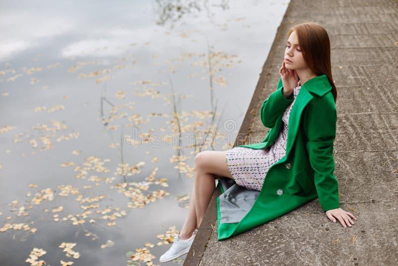 Het meisje in een groene laag loopt langs de meerdijk op een bewolkte de herfstdag De herfstmanier en kleding, gele gevallen blad royalty-vrije stock afbeelding