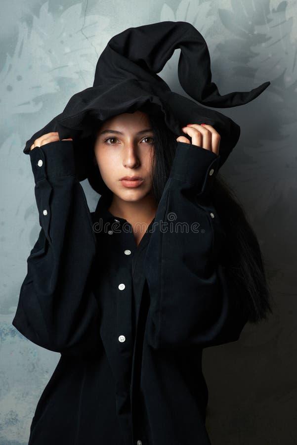 Het meisje in een heksenkostuum kijkt mysteriously royalty-vrije stock foto